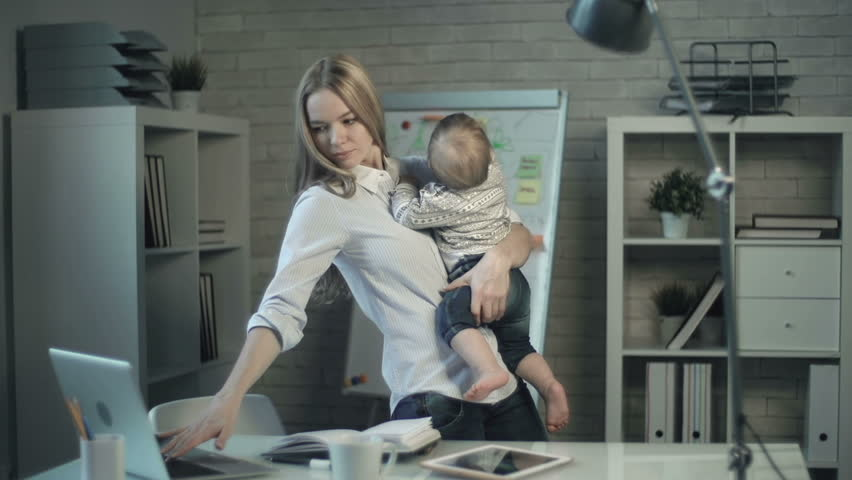 Close up of mother rocking a child in her arms and working at laptop at the same time