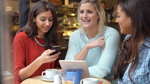 Three women sitting at table in caf_ take a selfie on mobile phone. Shot on Sony FS700 at a frame rate of 25fps