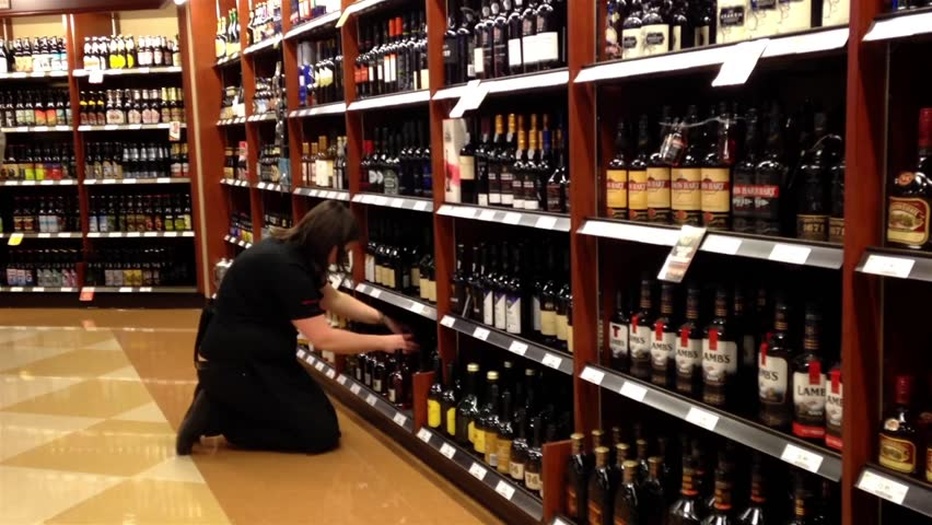 Pitt Meadows, BC, Canada - March 14, 2015 : Worker exhibiting wine on the display rack inside BC liquor store