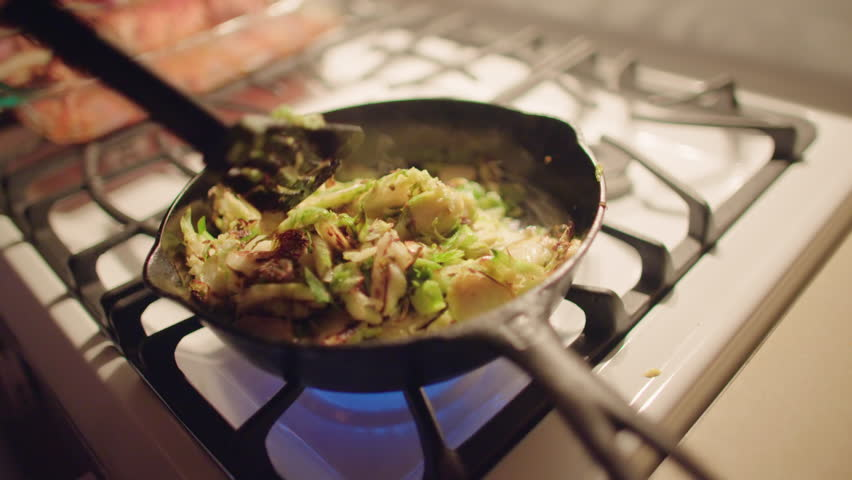 Close up on cook's hands with spatula, finishing frying sprouts in a pan on top of gas stove.  Hand held camera, slow motion recorded at 60fps.