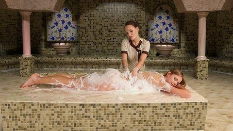 Girl enjoys of turetskim massage in hammam . Camera moves . Used dolly system