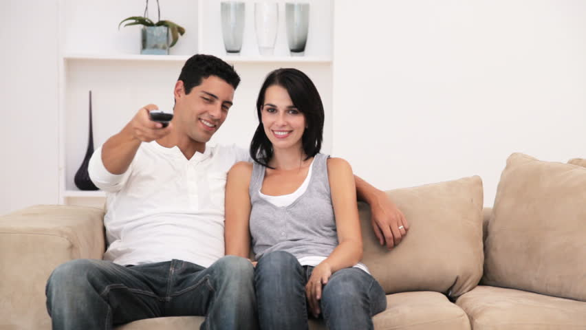 Young Couple Watching Television and Teasing Each other with the Remote Control