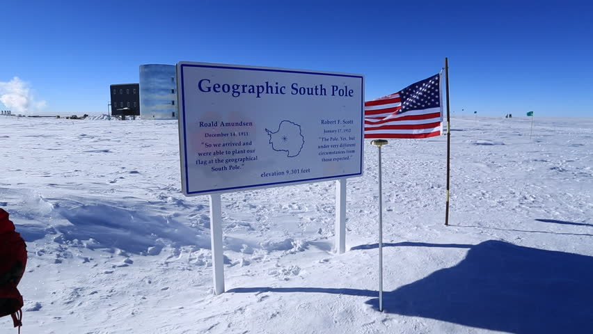 Geographic South Pole sign with Amundsen-Scott South Pole station behind