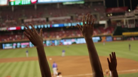 Two hands stick out and cheer during a baseball game. Gravel, green grass and baseball players soft focus in the background.