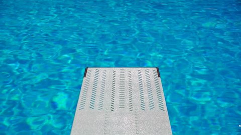 View from a trampoline in an Olympic sport diving swimming pool with beautiful clear blue water full of light reflections, stock footage in real time