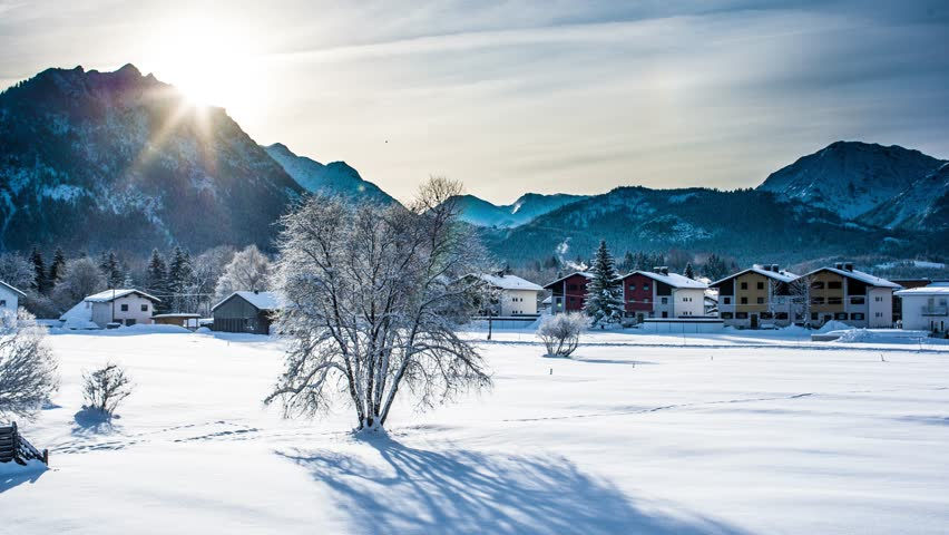 Timelapse of Alpine mountain morning, 4K, UHD. Picturesque landscape time lapse of the early winter morning in the small village in the Alps mountains in Austria. Winter travel and holiday concept.