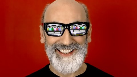 An old man with hypnotic glasses, with analogue old CRT TV test card with color bars, full of noise, static, grain, scanlines. He hides his face. Close-up shot, red background.