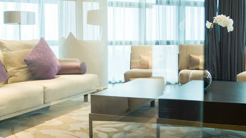 : Luxury apartment interior. View of beautifully decorated living room with beige sofa and orchid on the table with lots of natural light