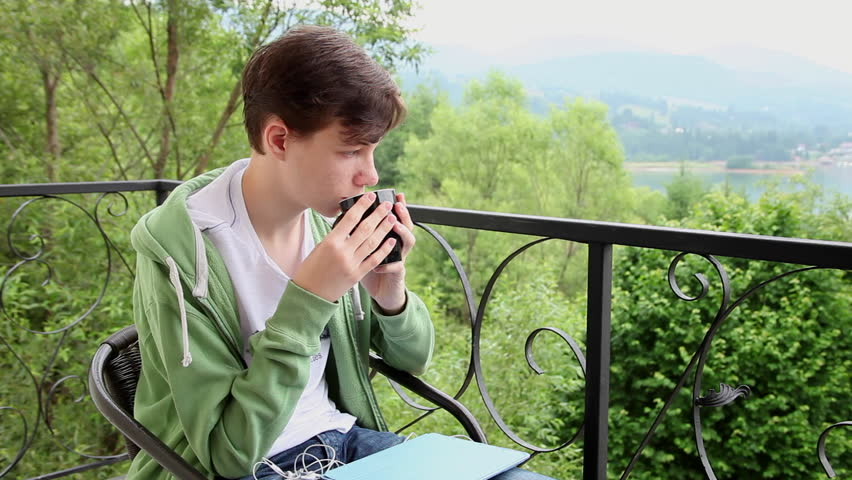 Young man drinking hot tea, coffee, balcony, outdoors, relaxing, vacation