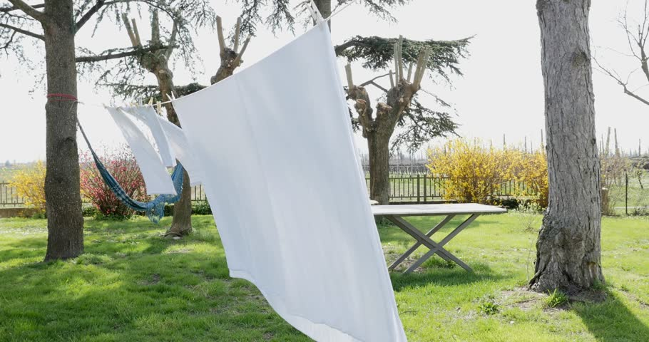 Fresh clean white sheets drying on washing line outdoors.