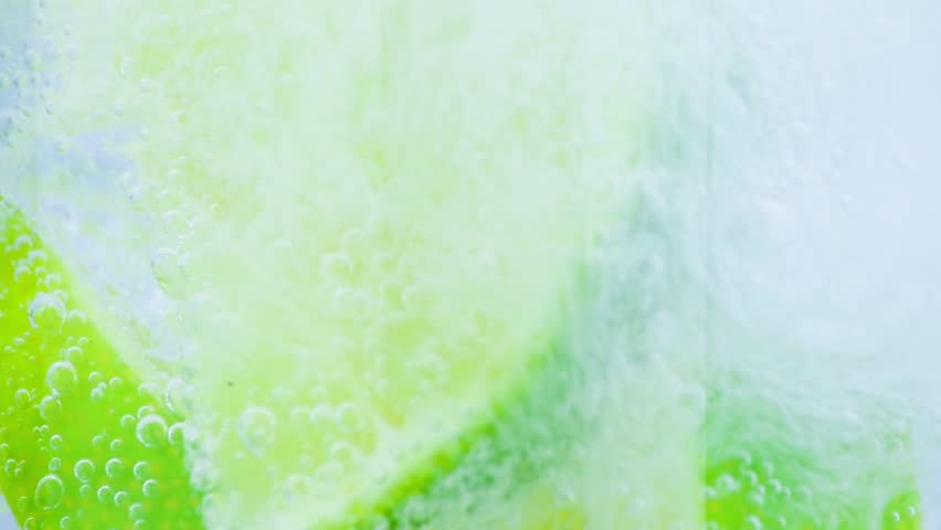 sparkling water with ice and slices lime on white background #9443303