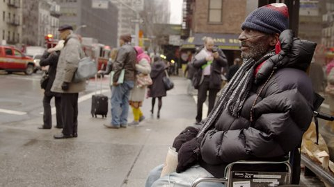 NEW YORK - MARCH 26, 2015: poverty-stricken man in wheelchair with cup, begging for change in 4k, Manhattan NY. Homelessness is a major problem in New York City.
