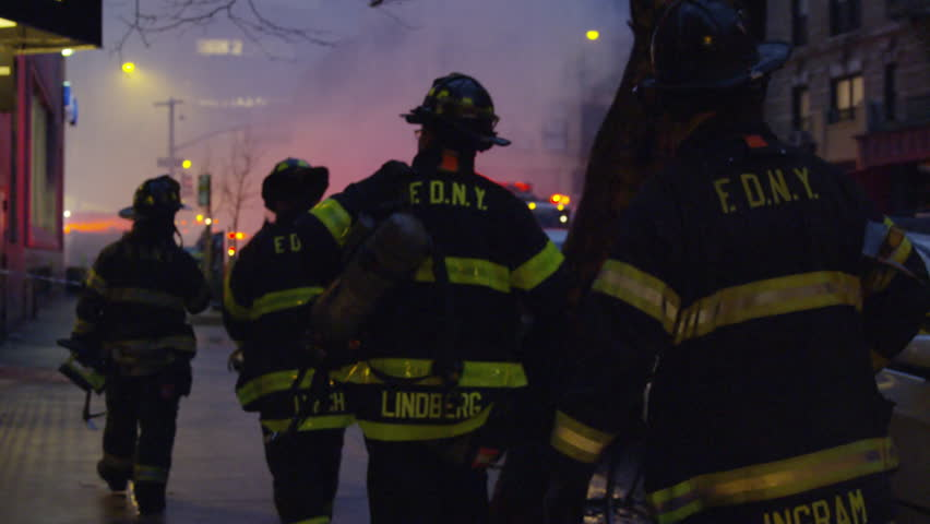 NEW YORK - MARCH 26, 2015: FDNY firefighters walking toward fire and smoke, silhouetted, slow motion in 4k, Manhattan NYC. FDNY responded to disaster; building collapse and fires in East Village.