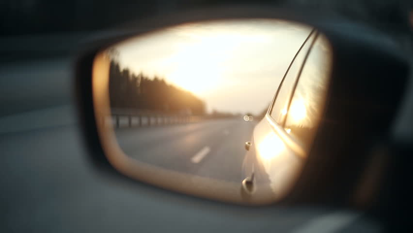 View of the road in the rearview mirror of a car at sunset
