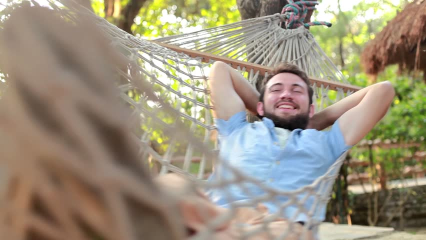 Bearded caucasian man lying down and swinging in a hammock on a summer day | Shutterstock HD Video #9460859