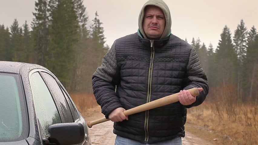 Aggressive man with a baseball bat near car in rainy day