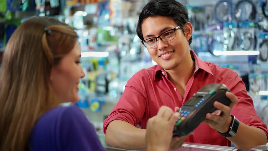 Young woman paying with credit card in computer shop, with asian sales clerk smiling and holding pos. The girl enters security code and waits for receipt