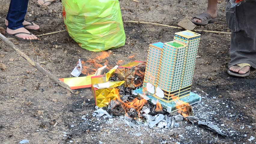 Burn joss paper or hell money Chinese Culture in The Qingming Festival at Sritasala Cemetery in Ratchaburi, Thailand.