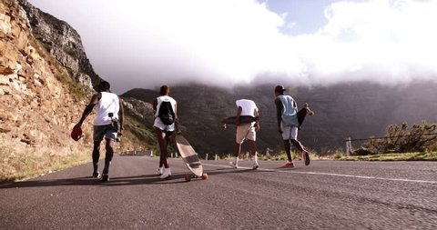 Rear view slow motion video of a group of teenage skater friends walking on mountain road with longboards together in Slow Motion