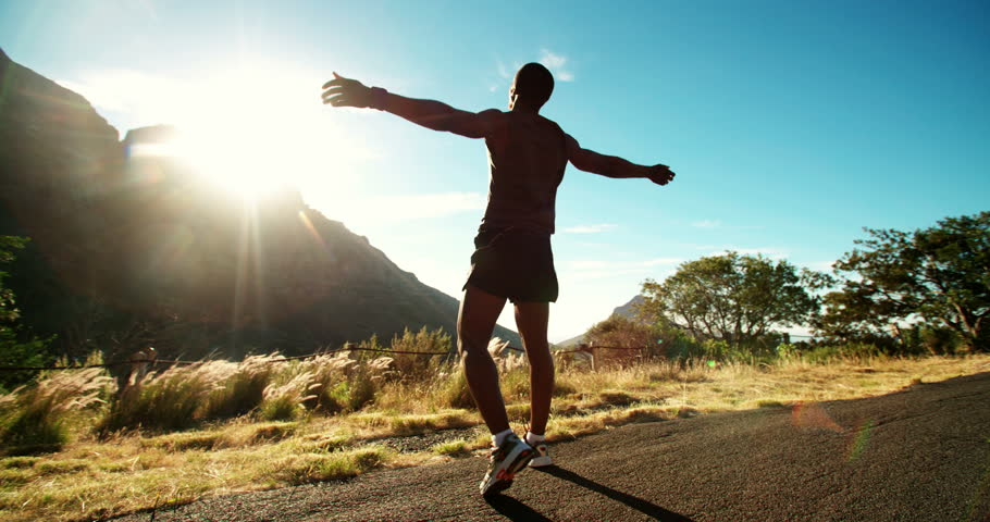Athlete leaping into the air in triumphant joy in beautiful natural surrounds slow motion