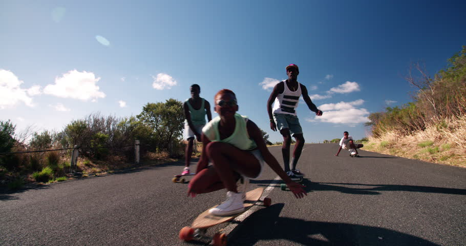 Mixed group of teenaged skateboarders racing each other downhill on a deserted road in Slow Motion