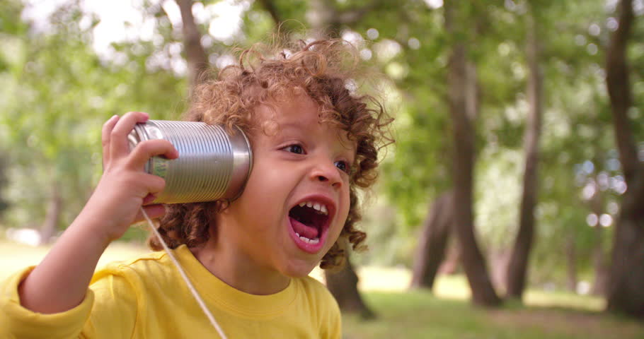 Interested little boy listening and talking through a tin can phone in a park