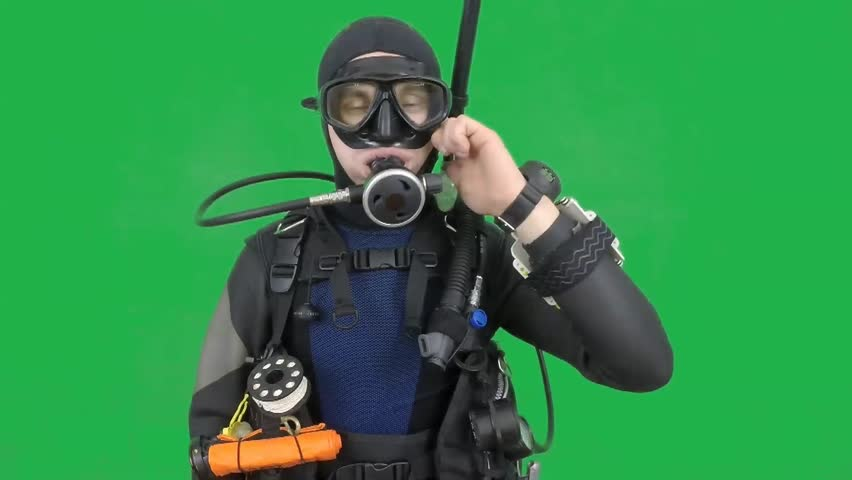 Dive instructor shows sing:TROUBLE WITH EAR also a available on the green screen all of diving sings from course  with full dive gear (open water diver)
