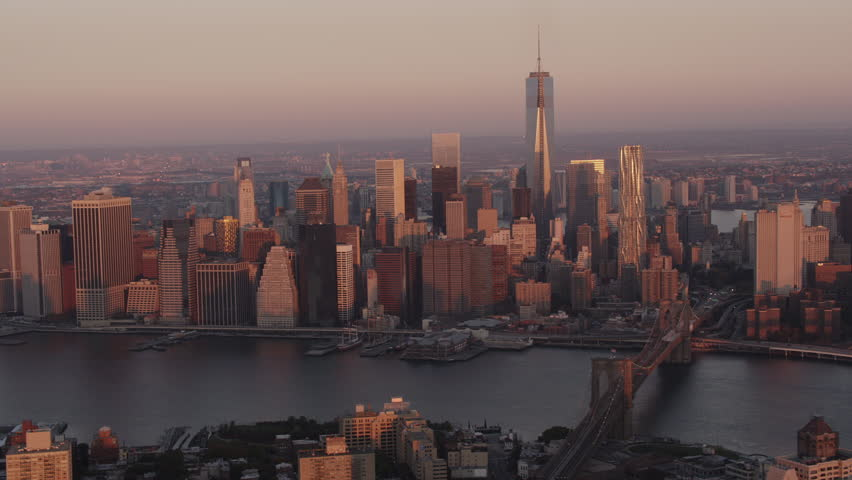 Aerial sunrise New York City skyline view of lower and Midtown Manhattan.  Shot from helicopter with Freedom Tower, Empire State Building, Brooklyn Bridge and East River in shot.  | Shutterstock HD Video #9536270