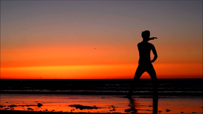Silhouette of man doing Tai Chi at sunset on the beach.