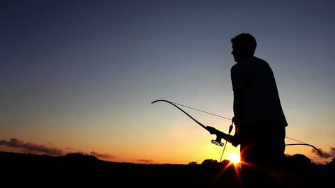 Archery silhouette, sun sets behind the archer