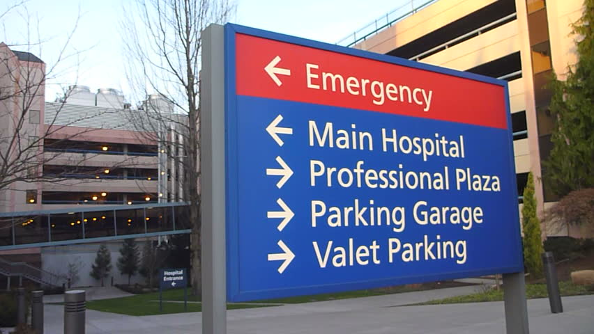 Hospital entrance exterior with sign pointing to emergency, main hospital and parking.