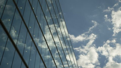 Moving clouds reflect onto office windows Time lapse of clouds reflecting onto the glass of a large office building.