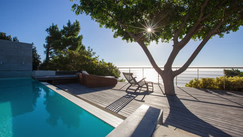 4K video of sunset timelapse. Sun going down over the ocean. Pool deck scene with big beautiful tree.
