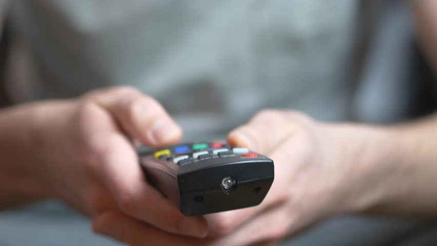 Male hand using a black casual tv remote controle to switch channels on television. | Shutterstock HD Video #9603590