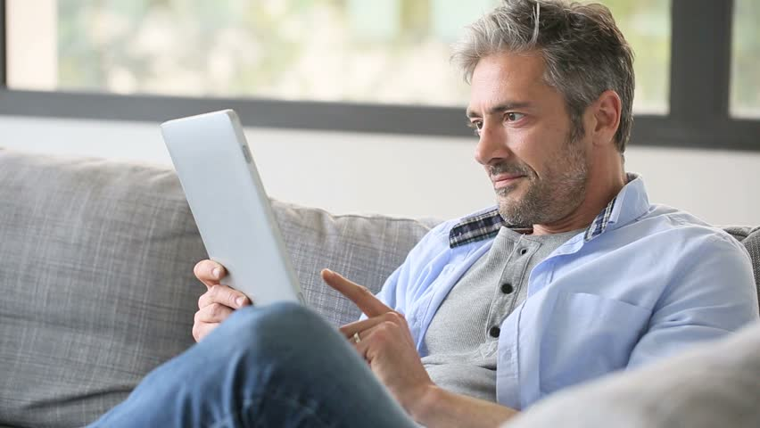 Mature man websurfing on internet with tablet