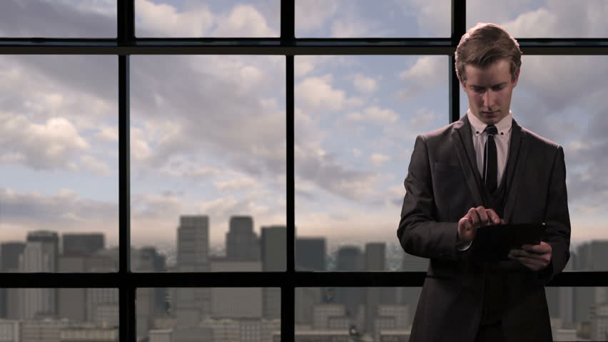 A young businessman using a tablet computer device by a view of a modern skyline with skyscrapers. Illustrating business concepts such as communication, networking and ICT. Room for copy to be added.