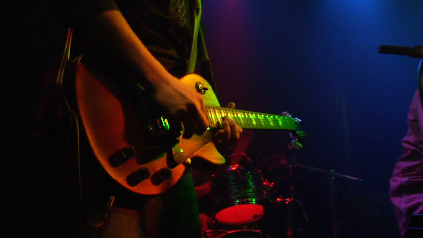This is a close up shot of a man playing a guitar at a rock concert at a popular club on the Sunset Strip in Los Angeles.