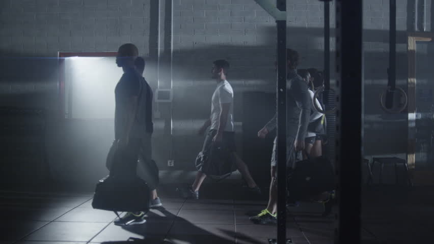 Young men and women entering a gym, medium shot slow mo POV from side angle