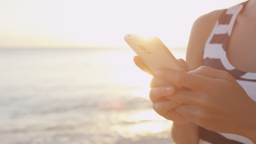 Woman texting on smartphone. Female is using mobile cell smart phone app at beach during sunset. Waves are rushing towards her. Sun is shining in background.
