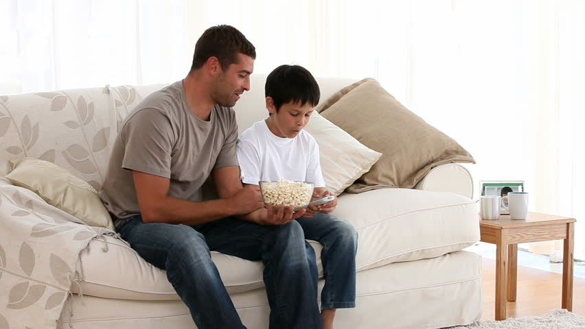 Father Eating Popcorn With His Son On A Sofa   HD Stock Video Clip
