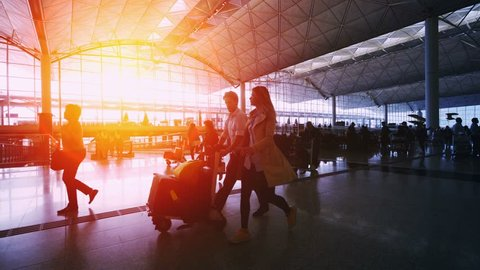 Sunset Silhouettes of TravelersCommuters in Airport. Beautiful wide panoramic view of the main hall of an airport.  Location: Hong Kong International Airport