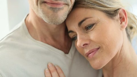 Mature couple embracing each other at home