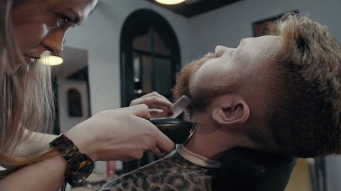 Barber woman trimming beard of client with clipper at barbershop. Slow motion
