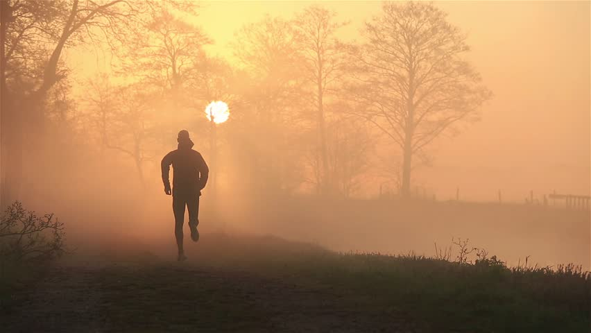 Silhouette of a man running in the countryside during a foggy, spring sunrise.