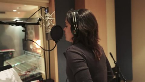 Shot of a female singer recording at a Music Studio