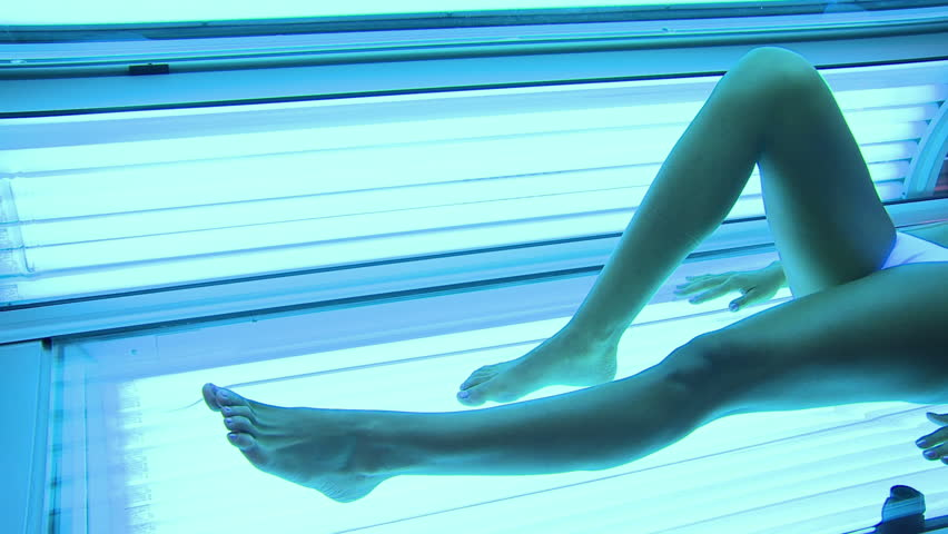 Smiling girl makes a ultraviolet lamp at beauty center. Serene young woman lying for a sunlamp. at spa center. Beautiful woman in a swimsuit at solarium looking at camera.