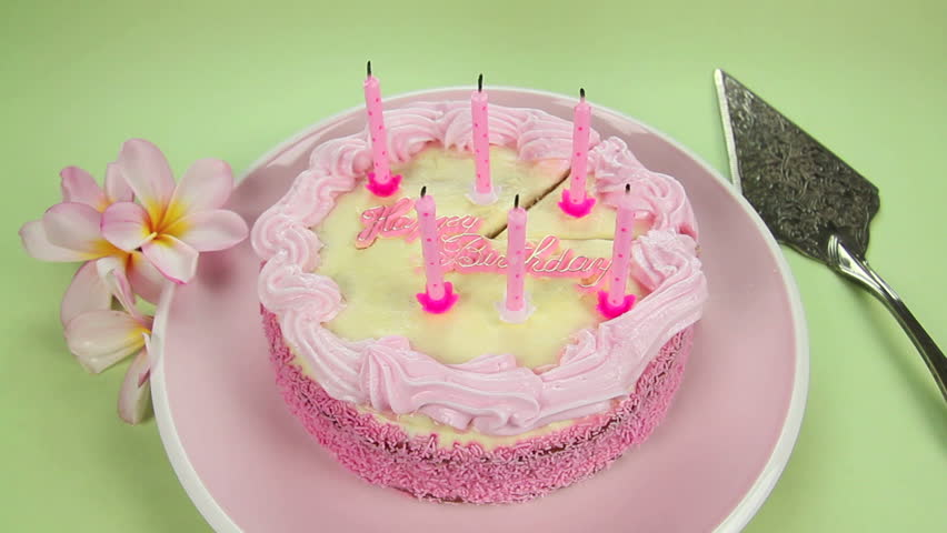 Edited sequence of birthday cake candles being blown out then the cake sliced.
