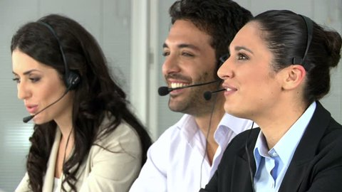 Beautiful young woman talking on headset at call center office. Smiling girl working at call center whit her colleagues. Happy switchboard operator working and looking at camera.