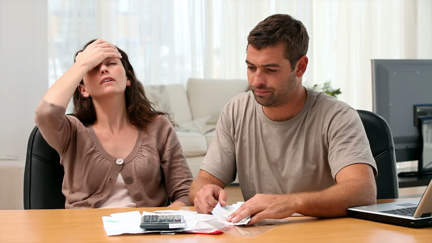 Couple studying their bills at home