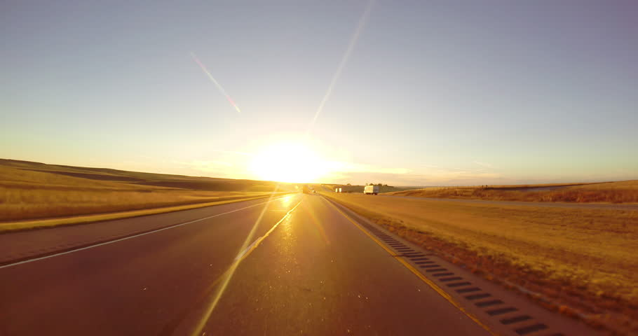 Driving down a highway at sunset along wheat fields | Shutterstock HD Video #9764600